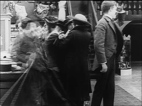 charlie chaplin putting hands on counter back kicking man in dept store - 1916 stock videos & royalty-free footage