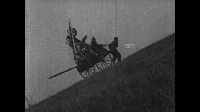 1915 charlie chaplin struggles to pull horse cart up hill - sklaverei stock-videos und b-roll-filmmaterial