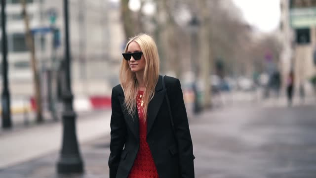 stockvideo's en b-roll-footage met charlotte groeneveld wears a black long coat, a red fringed wool dress, red balenciaga shoes, a brown leather bag, outside altuzarra, during paris... - zoom out