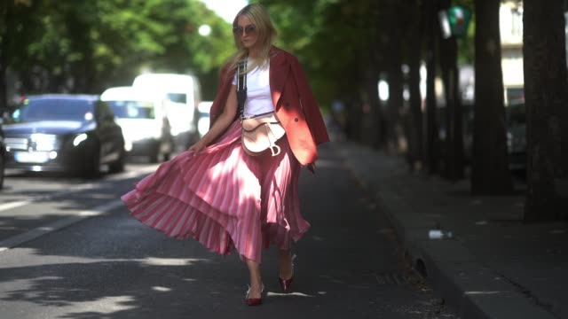 vídeos y material grabado en eventos de stock de charlotte groeneveld wears outside dior sunglassesa white top a dior bag a light rustcolor jacket a lustrous pink pleated skirt shiny dior pointy... - falda