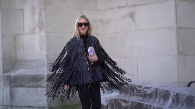 Charlotte Groeneveld wears sunglasses a black leather fringed jacket sneakers shoes outside Elie Saab during Paris Fashion Week Womenswear...