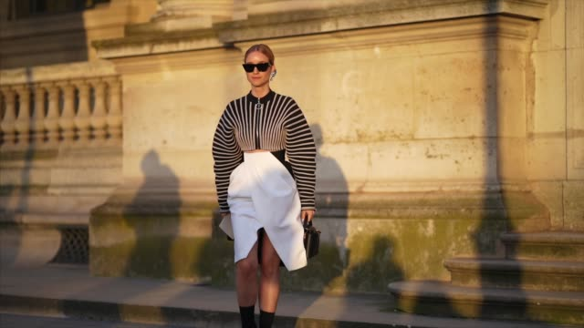 charlotte groeneveld wears sunglasses, earrings, a striped jacket with large sleeves, a white skirt, black boots, a bag, outside vuitton, during... - autumn stock videos & royalty-free footage