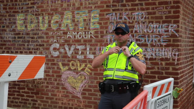08112018 charlottesville virginia usa police guard a barricade on water street near a memorial a year after the death of heather heyer when a neonazi... - barricade stock videos & royalty-free footage