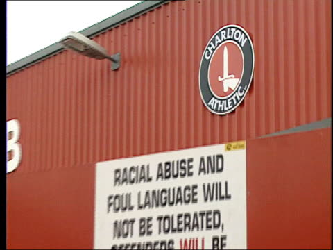 EXT 'Charlton Athletic' sign on wall of football stadium PULL OUT sign warning fans against racist abuse 'Let's kick racism out of football' poster