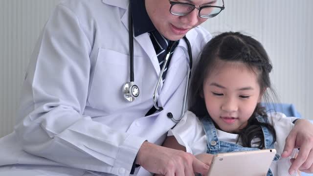 vidéos et rushes de charmante petite fille asiatique d'âge 6 ans avec le mâle asiatique de pédiatre sur la vidéoconférence pour l'appel vidéo à sa mère ou parents pendant la distanciation sociale pour empêcher des épidémies de coronavirus ou de covid-19 tandis  - new age concept