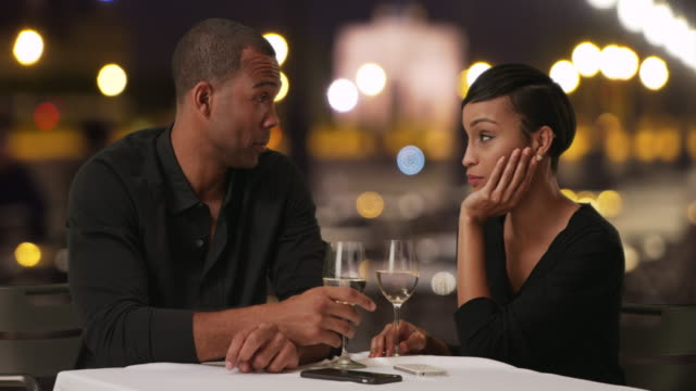 charming black male tells his lovely date something funny while drinking wine - handsome people stock videos & royalty-free footage