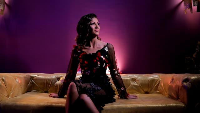 vídeos de stock, filmes e b-roll de encantadora morena sentada no sofá colorido ouro - de pernas cruzadas
