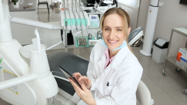charming dentist using digital tablet - contented emotion stock videos & royalty-free footage