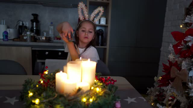 charming girl wearing costume rabbit ears and lighting the christmas candles with a candle lighter - rabbit costume stock videos & royalty-free footage
