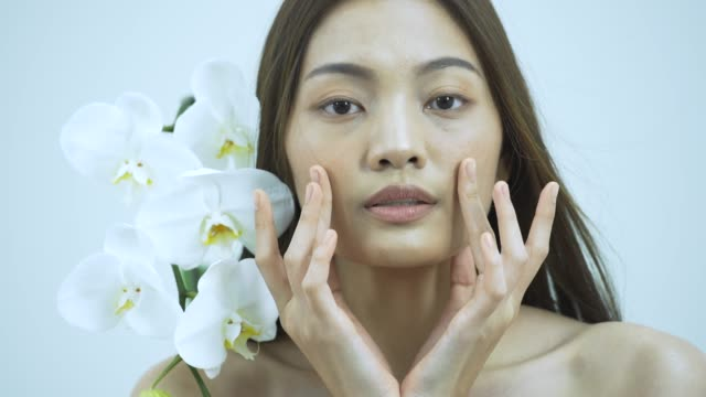 charming  healthy woman touching smooth skin on face with flower - skin feature stock videos & royalty-free footage