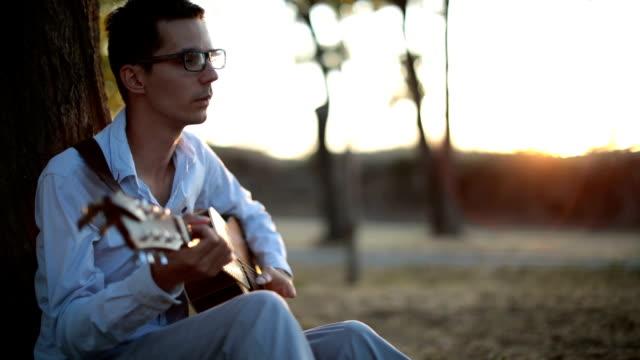 vídeos de stock, filmes e b-roll de homem charmoso, tocando guitarra - cantora