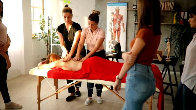 vidéos et rushes de charmant massothérapeute présentant à ses élèves comment donner correctement le massage de retour - banc de massage