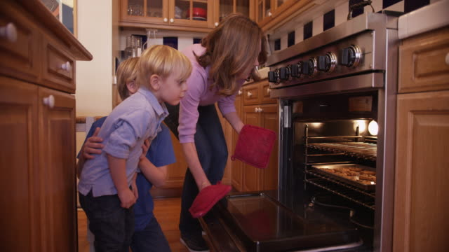 charming mother baking cookies for her two boys - oven stock videos & royalty-free footage