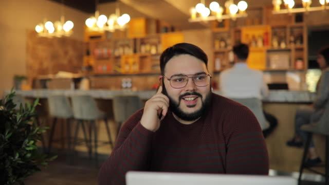 vídeos de stock e filmes b-roll de charming overweight man talking on mobile in cafe - usar portátil