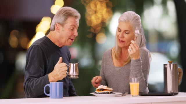 vídeos de stock, filmes e b-roll de charming senior white couple tasting cooking sauce - xarope