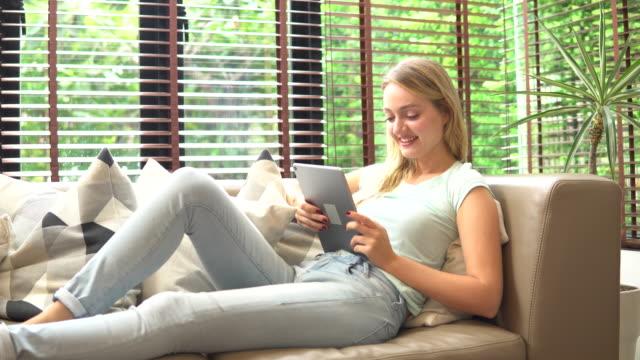 vídeos y material grabado en eventos de stock de mujer encantadora disfrutar utilizando el ordenador en casa mintiendo en un sofá en una sala de estar - magazine