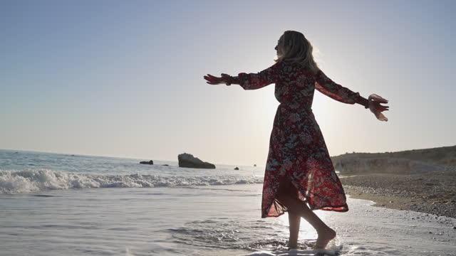 vídeos de stock, filmes e b-roll de mulher encantadora em vestido vermelho, absorve raios solares do pôr do sol e desfruta da energia calma que ela reive do mar - pedra solta