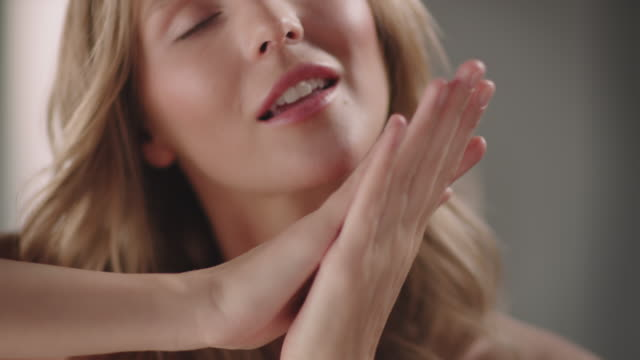 charming woman smiling while caressing her hands - strofinare toccare video stock e b–roll