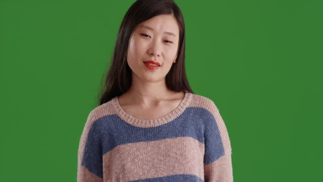 vídeos de stock e filmes b-roll de charming young asian student smiling with hair blowing in front of green screen - cabelo natural