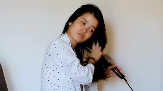 魅力的な若いアジア女性はヘアー ドライヤーに寝室のベッドの上に座って、彼女の長い髪を乾燥します。 - 衣類乾燥機点の映像素材/bロール