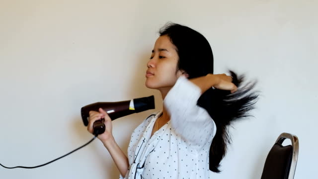 charming young asian woman dries the hair dryer her long hair, sitting on the bed in the bedroom. - drying stock videos and b-roll footage