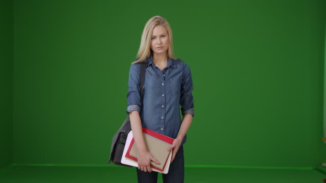 Charming young female student on her way to class on green screen