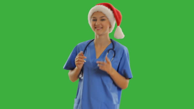charming young nurse showing copy space - santa hat stock videos & royalty-free footage