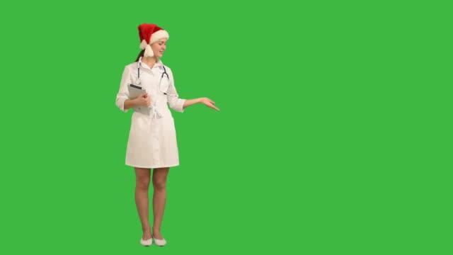 Charmante junge Krankenschwester zeigt Textfreiraum und zeigt seine Daumen auf grünem Hintergrund