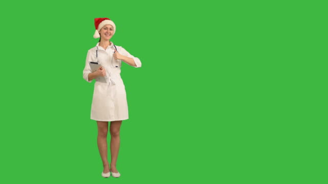 charming young nurse shows the copy space and shows his thumb on green background - santa hat stock videos & royalty-free footage
