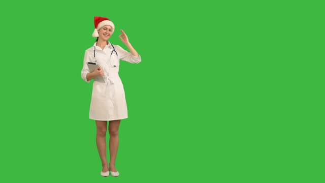 charming young nurse shows the copy space and shows ok on green background - santa hat stock videos & royalty-free footage