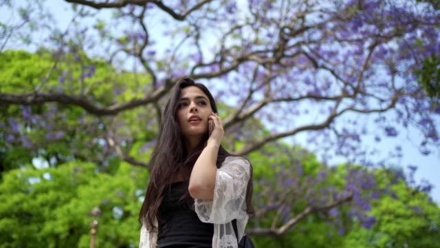 vídeos y material grabado en eventos de stock de encantadora joven disfrutando de un relajante paseo en el parque público y hablando por teléfono móvil - cool attitude