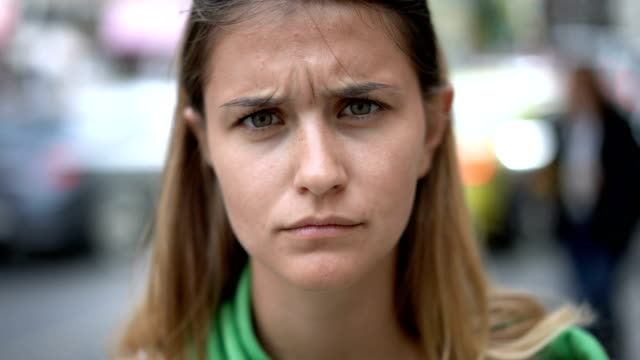 charming young woman making faces at camera - frowning stock videos & royalty-free footage