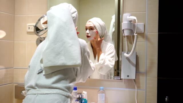vídeos de stock, filmes e b-roll de mulher nova charming com máscara facial em sua face - máscara