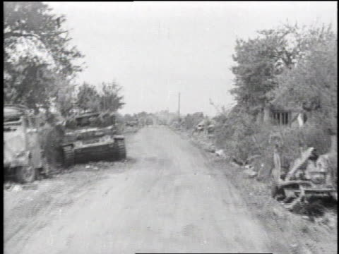 charred corpse with arms reaching out / soldiers lifting dead body from tank turret / traveling down road with destroyed vehicles lying on each side... - 1944 bildbanksvideor och videomaterial från bakom kulisserna