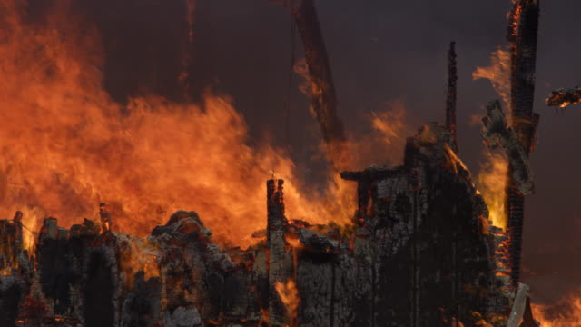 Charred, still blazing remains of a house consumed by fire