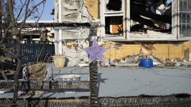 Charred wood by front of destroyed house