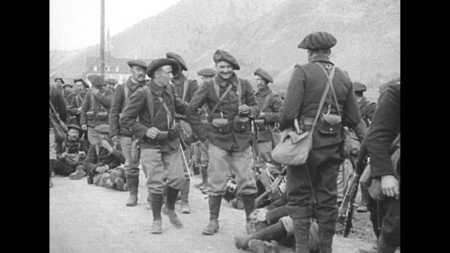 chasseurs alpins resting on side of mountain road during world war i, some sitting, some wearing berets and smoking cigarettes walking towards camera... - basco video stock e b–roll