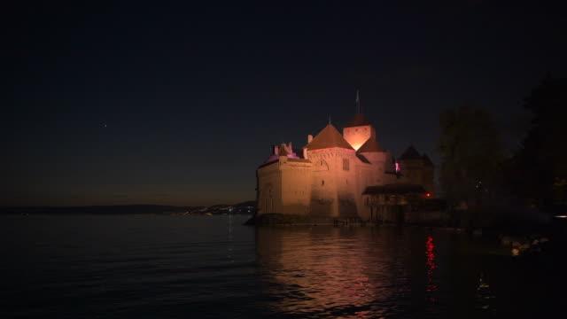 Chateau de Chillon (Chillon Castle) on the shore of Lake Geneva illuminated at night.