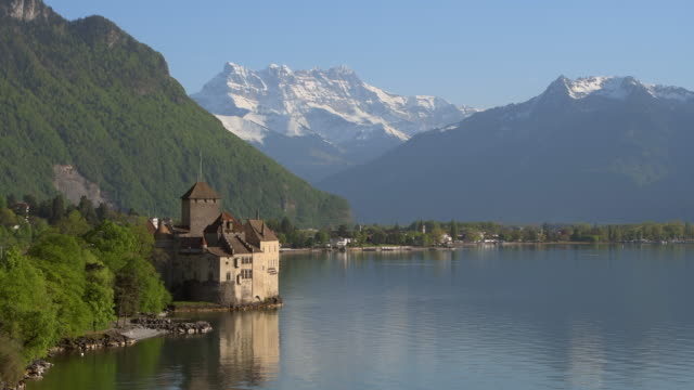 chateau de chillon (chillon castle) on the shore of lake geneva with snow covered mountains (dents du midi) in background, clear blue sky. chillon castle, montreux, lake geneva, vaud canton, riviera-pays-d'enhaut, switzerland, europe. - lake geneva stock videos & royalty-free footage