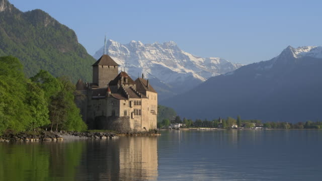chateau de chillon (chillon castle) on the shore of lake geneva with snow covered mountains (dents du midi) in background, clear blue sky. chillon castle, montreux, lake geneva, vaud canton, riviera-pays-d'enhaut, switzerland, europe. - montreux stock videos and b-roll footage