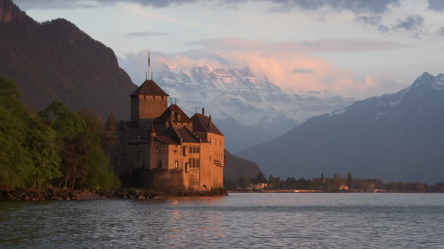 chateau de chillon (chillon castle) on the shore of lake geneva with snow covered mountains (dents du midi) in background at dramatic sunset scenery. - montreux stock videos and b-roll footage