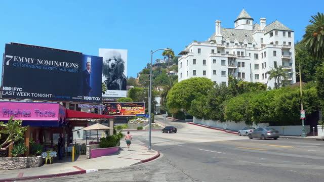chateau marmont hotel and cars traffic on sunset strip on sunset boulevard at rush hour near giant movie billboard in los angeles, california, 4k - rush hour 2 bildbanksvideor och videomaterial från bakom kulisserna