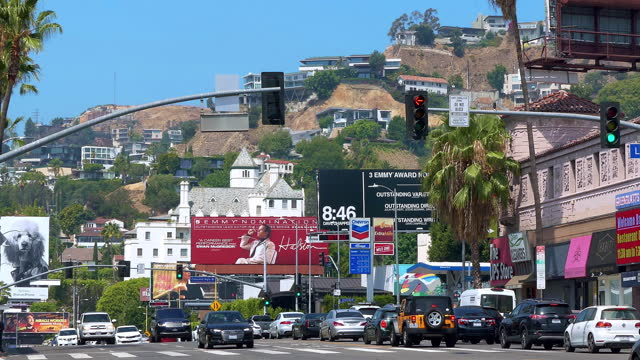 chateau marmont hotel and luxury cars traffic on sunset strip on sunset boulevard at rush hour near giant movie billboard in los angeles, california, 4k - rush hour 2 bildbanksvideor och videomaterial från bakom kulisserna
