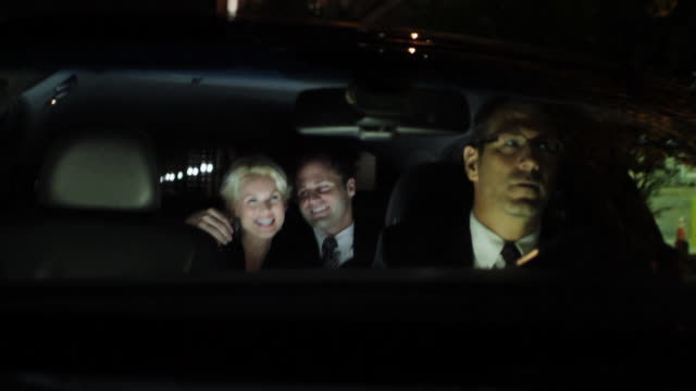 ms pov chauffeur driving car through city and couple in back seat - chauffeur stock videos and b-roll footage