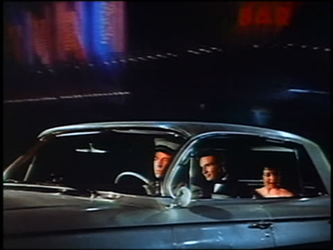 1961 chauffeur driving couple in Cadillac / projected scenery in background / Cupids appear above car