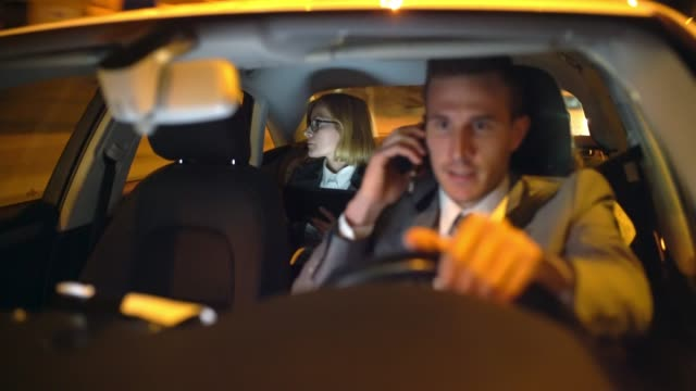 ws chauffeur having a call while driving a businesswoman in the back seat of a limousine - taxi video stock e b–roll