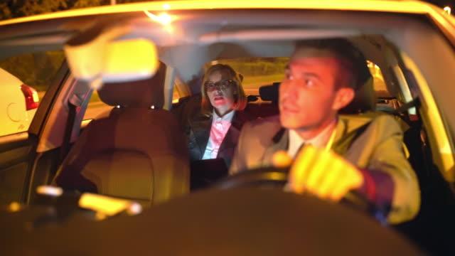 vídeos de stock, filmes e b-roll de motorista de ws tendo uma conversa com uma mulher de negócios sentado no banco de trás de uma limusine - táxi