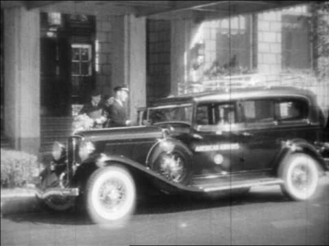 B/W 1933 chauffeur holding open door for people entering American Airlines limo / industrial