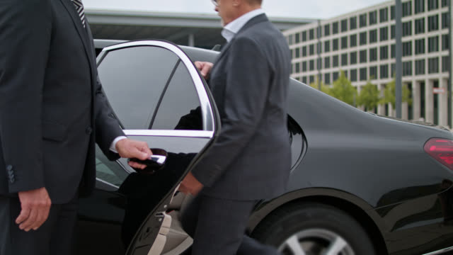 vidéos et rushes de chauffeur in full suit is opening door of black limousine with discretion, senior vip hon businessman enters the car end gets chauffeured away - limousine voiture