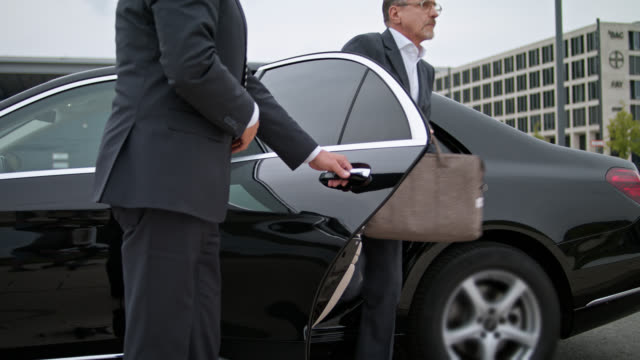 vídeos y material grabado en eventos de stock de chauffeur opens back door of black limousine with discretion, senior vip businessman is exiting the car and in the end the car is driving off - protection